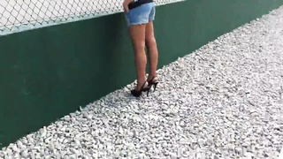Lovely brown-haired beauty with large tits gives a blowjob in public place